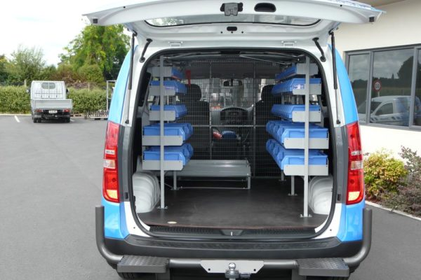 Pair of shelving units in rear of van with Roll-a-table to contain threading machine